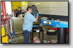 Mechanic Working on Wheel at Precise Auto Service